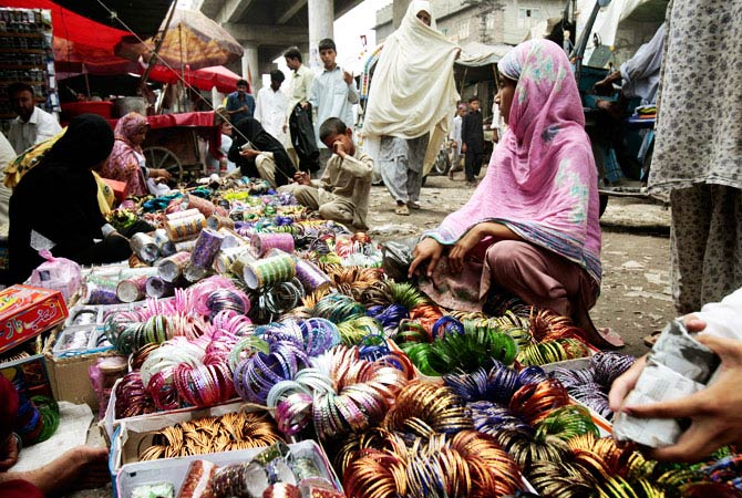 Pakistani women display traditional bangles for sale in preparation for the upcoming Eid al-Fitr festival in a market in Peshawar. - Photo by AP