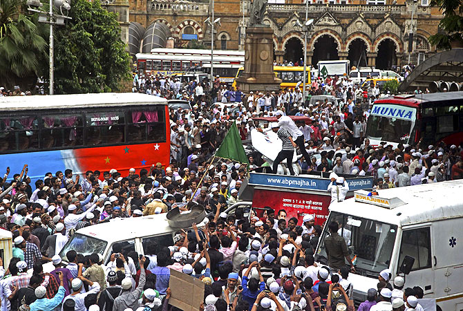 Protestors block traffic and damage media vehicles during a demonstration against the deaths of Muslims in recent violence in Assam, in Mumbai. -Photo by AP