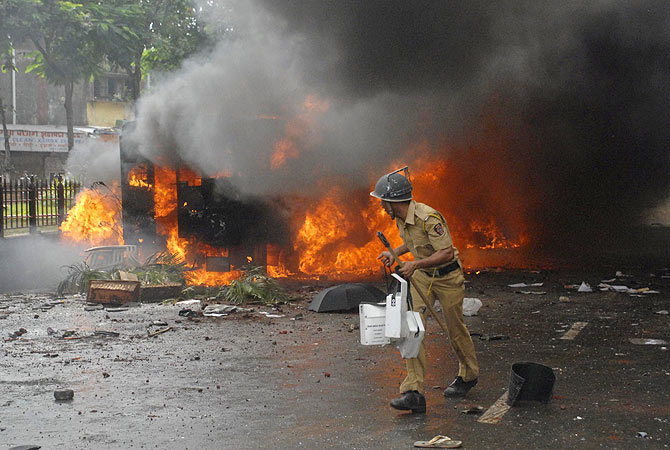 A policeman walks past a burning vehicle during a protest in Mumbai. -Photo by Reuters