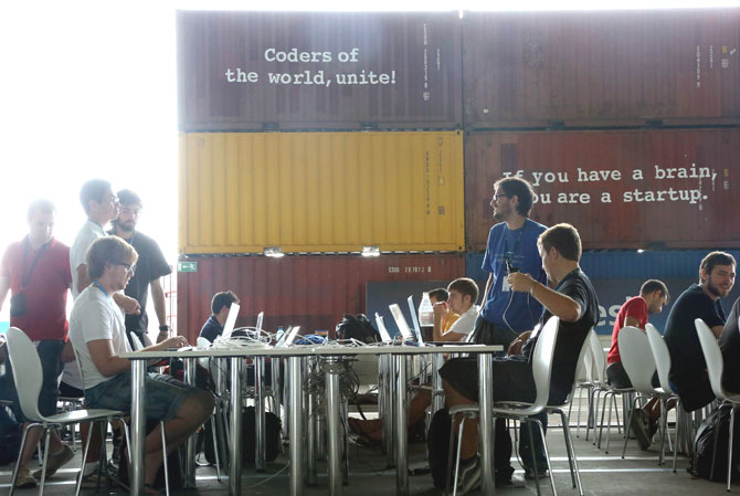 Young men sit with their laptops at the event in a hangar on the premises of the former airport Tempelhof  in Berlin.