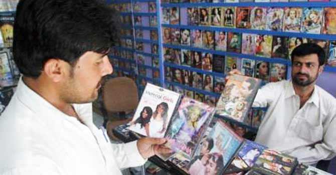 A man looks at CDs and DVDs at a shop in Charsadda. – File photo by Reuters
