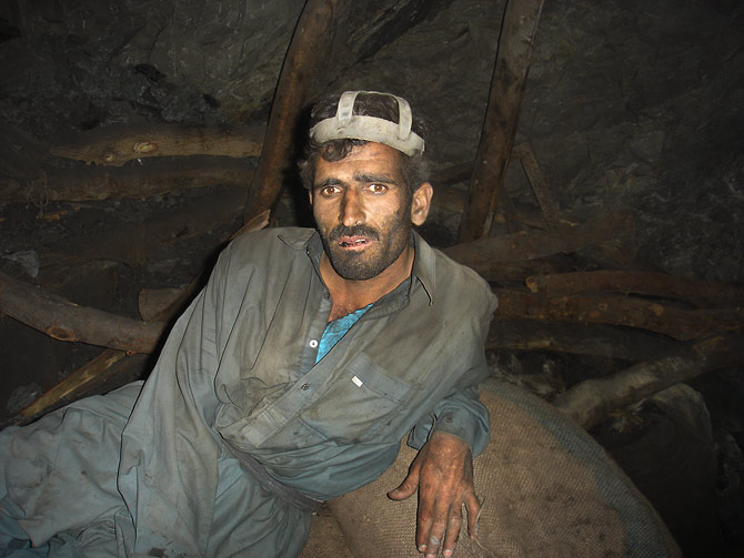 A tired miner sits on a coal sack, waiting for the supervisor to ring the bell so that he can go up. Mining in Balochistan is said to be the most difficult in the world.