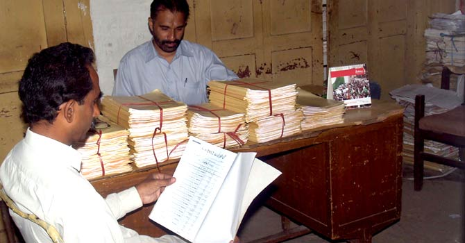 Officials at the Election Commission of Pakistan office in Karachi display and check electoral lists. — Dawn photo