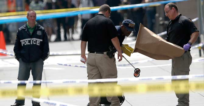 Officials collect evidence near the Empire State Building following a shooting, Friday, Aug. 24, 2012, in New York. — Photo by AP