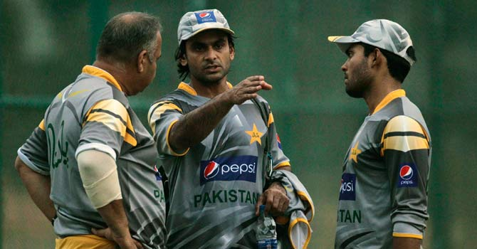 Mohammad Hafeez chats with team coach Dav Whatmore, left, and teammate Umar Akmal during a practice session in Sri Lanka in June. – Photo by AP