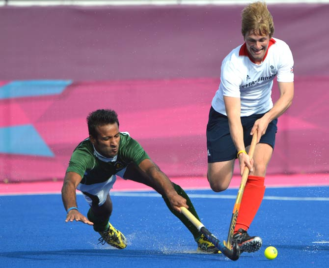 Asley Jackson of Britain (R) dribbles past Muhammad Irfan of Pakistan. - Photo by AFP.