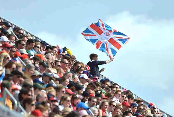 A British supporter waves a British flag reading ?Team GB? from the stands. - Photo by AFP.