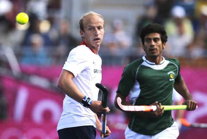 Britain's Glenn Kirkham, left, watches the ball during a men's hockey preliminary round match against Pakistan. - Photo by AP.