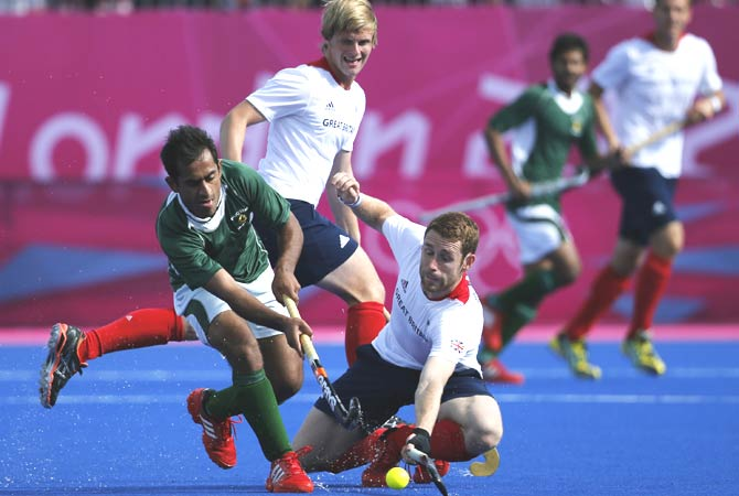 Pakistan's Fareed Ahmed, left, and Britain's Jonty Clarke vie for the ball as Britain's Ashley Jackson, back, watches, during their match. -Photo by AP.