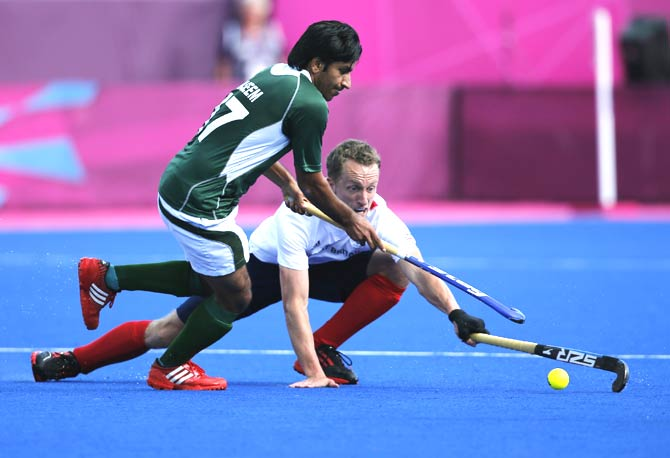 Pakistan's Ahmad Waseem, right, and Britain's Dan Fox vie for the ball. - Photo by AP.