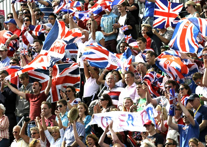 Fans wave British flags while cheering for Britain at the men's hockey preliminary match against Pakistan. - Photo by AP.
