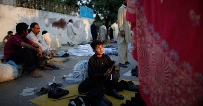 Asif Khan, 14, center, sells shoes in a market in Islamabad. – File photo by AP