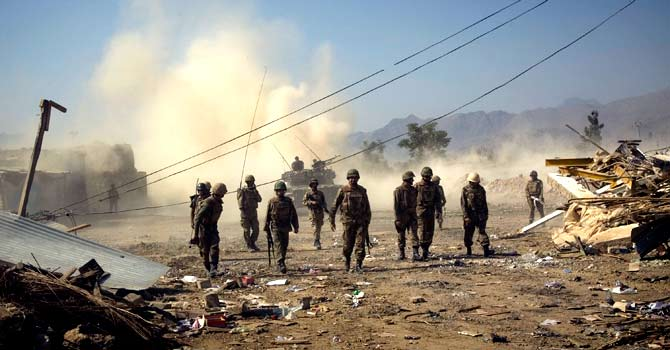 Army soldiers walk past damaged houses in Loi Sam, in the Bajur tribal region in 2008. – File photo by AP