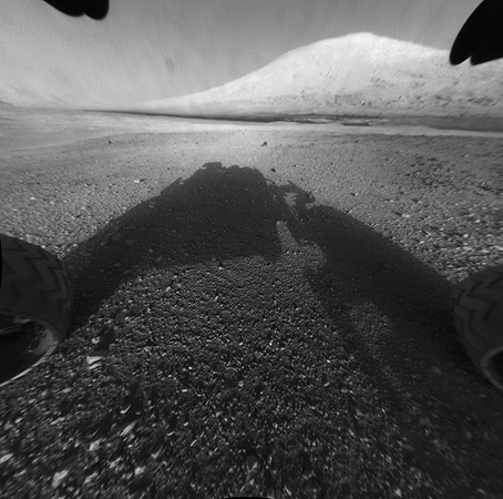This image taken by NASA's Curiosity shows what lies ahead for the rover -- its main science target, informally called Mount Sharp Monday, Aug. 6, 2012. The rover's shadow can be seen in the foreground, and the dark bands beyond are dunes. Rising up in the distance is the highest peak of Mount Sharp at a height of about 3.4 miles (5.5 kilometers), taller than Mt. Whitney in California. The Curiosity team hopes to drive the rover to the mountain to investigate its lower layers, which scientists think hold clues to p