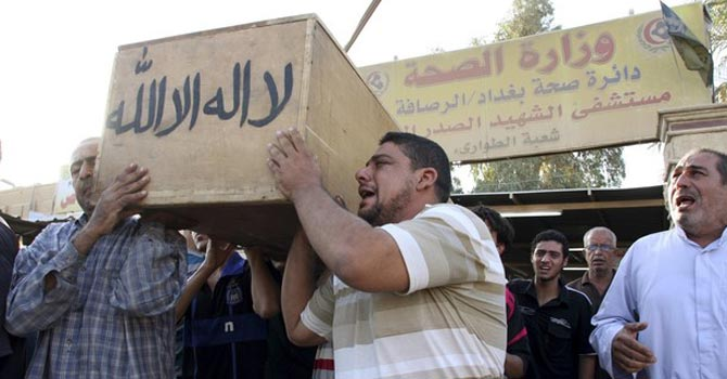 Men carry the coffin of a victim, killed in a bomb attack. — Reuters Photo