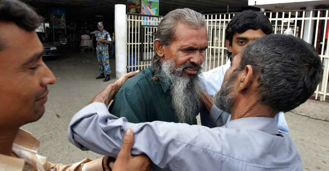 Moslemuddin Sarkar, 52, centre, who had been missing since 1989 is hugged by his brother Sekandar Ali, right, after he arrived at the airport in Dhaka, Bangladesh. For 23 years, Sarkar's family in Bangladesh thought he was dead. But then an anonymous caller informed a local official in May that he was alive and in jail in Pakistan. — Photo by AP