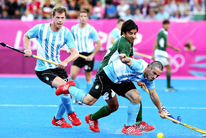 Argentina's Santiago Montelli , front, and Pakistan's Ahmed Waseem vie for the ball as Lucas Rossi, left, watches. -Photo by AP