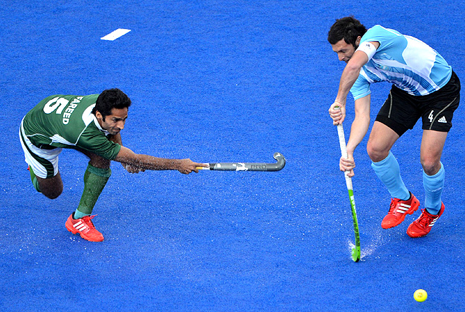 Pakistan's Fareed Ahmed (L) plays a shot against Argentina's Matias Damian Vila. -Photo by AFP