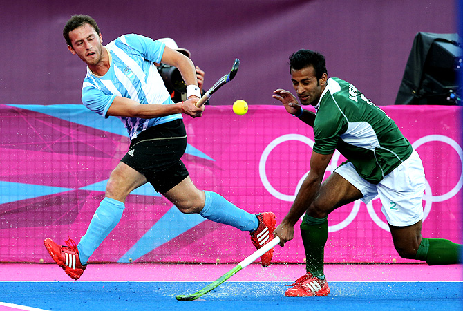 Argentina's Lucas Vila, left, and Pakistan's Fareed Ahmed vie for the ball. -Photo by AP