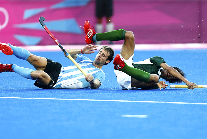 Pakistan's Muhammad Rizwan (R) and Argentina's Facundo Callioni fall. -Photo by Reuters