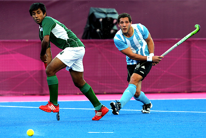 Argentina's Augustin Mazzilli, right, looks at the ball after playing a shot as Pakistan's Muhammad Tousiq runs. -Photo by AP