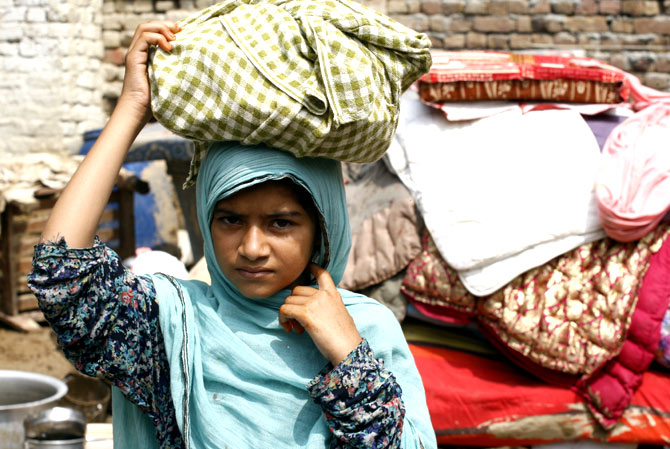 A flood-displaced girl carries her belongings in Nowshera, near Peshawar on Thursday, Aug. 23, 2012.
