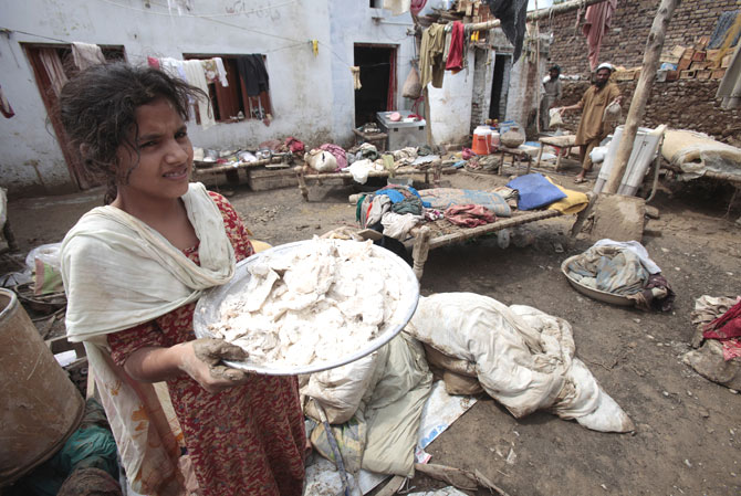 A girl carries flour spoiled by rain water.