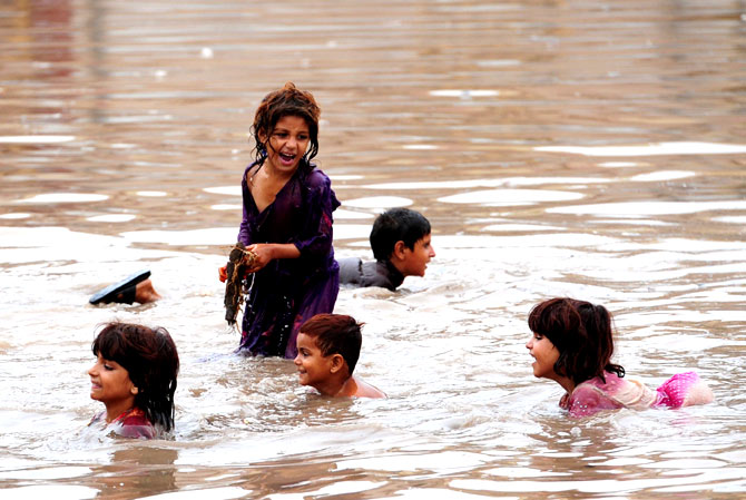 Children play in floodwaters following heavy rain in Aza Kheil, some 40 kms from Peshawar, on August 23, 2012.