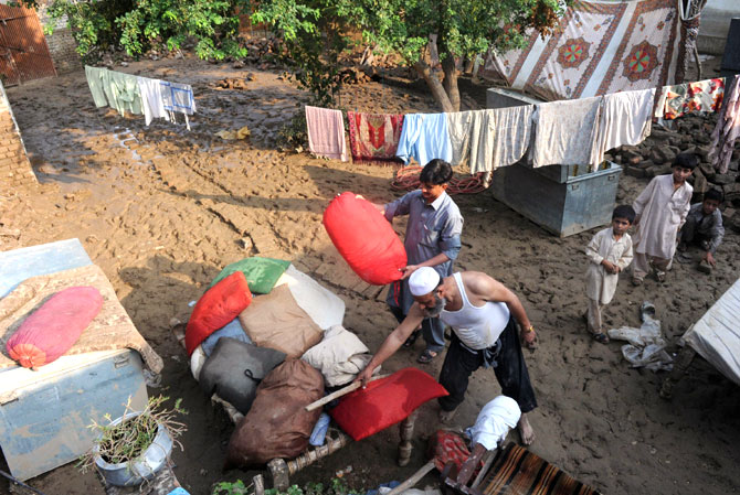 Residents place their belongings on a wooden bed after floodwaters inundated their house.