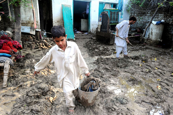 A resident and his son remove mud after floodwaters inundated his house.