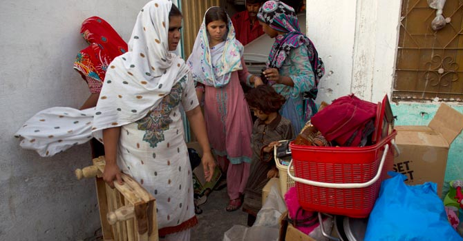 Pakistani Christian women collect their belongings to leave their home.— AP Photo