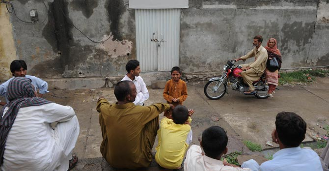 Pakistani residents gather outside the house of a Christian girl, who was arrested on charges of blasphemy. — AFP Photo