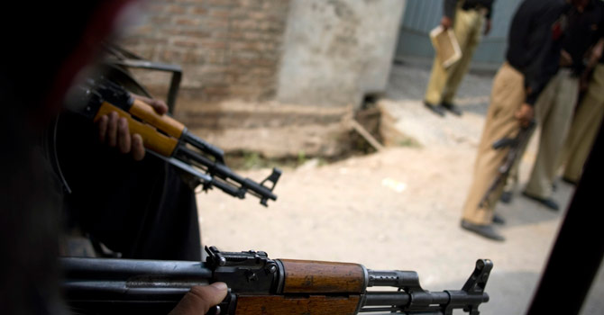 Police officers hold their weapons as they stand guard in Peshawar. – File photo by AP