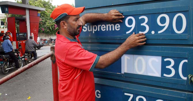 Fuel station employee displays new prices of petroleum products at a fuel station in Karachi on Wednesday, August 01, 2012. Pakistan Oil and Gas Regulatory Authority (OGRA) were increased petroleum products and CNG prices by up to 8.9 percent due to the global rise in oil. (S.Imran Ali/PPI Images).