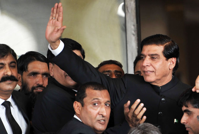 Pakistani Prime Minister Raja Pervez Ashraf (R) waves upon his arrival at The Supreme Court in Islamabad on August 27, 2012.