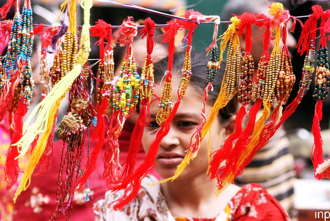 A girl selecting one of the crimson threads also called as Rakhi. - Photo by INP.