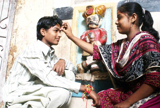 Hindu girl ties Rakhi on her brother's wrist as they celebrate Raksha Bandhan in their home. - Photo by INP.