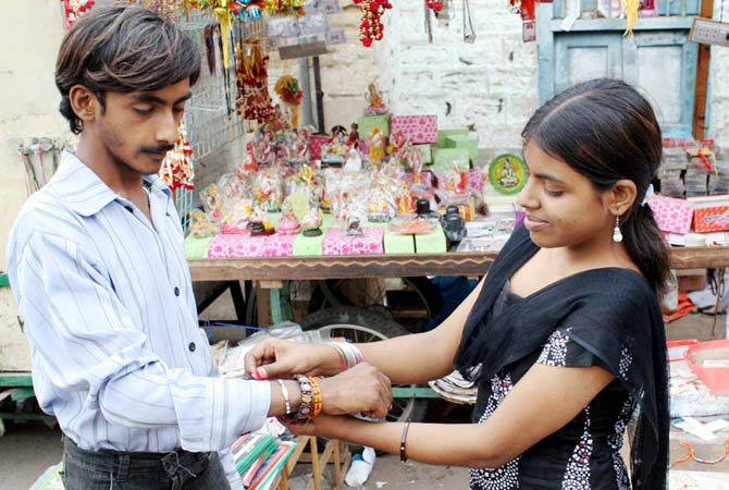Hindu girl ties Rakhi on the wrist of her brother. - Photo by PPI