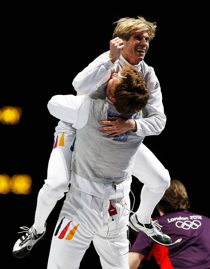 Germany's Andre Wessels and Peter Joppich (top) celebrate winning against the U.S. at the end of their men's foil team bronze medal fencing competition. - Photo by Reuters