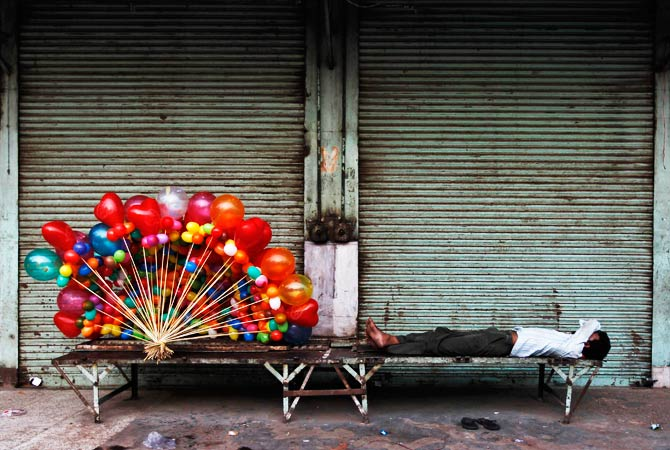 A balloon seller takes a nap in front of the closed shops on the occasion of Eid-al-Fitr. - Photo by Reuters