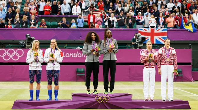 Gold medallists Serena Williams (center, L) and her sister Venus Williams of the U.S. are flanked by silver medallists Andrea Hlavackova (far left) and Lucie Hradecka of the Czech Republic and bronze medallists Nadia Petrova (far right) and Maria Kirilenko of Russia during the presentation ceremony for the women's doubles tennis. - Photo by Reuters