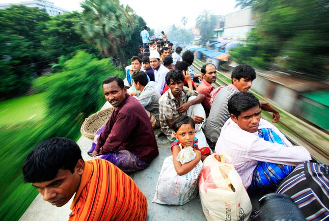 Passengers sit on top of an overcrowded train as it heads for Jamalpur from Dhaka August 16, 2012. Millions of residents in Dhaka are traveling home from the capital city to celebrate the Eid al-Fitr holiday. - Photo by Reuters
