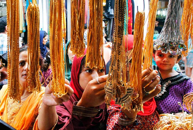 Women select jewelry before buying it from a vendor ahead of the Eid-al-Fitr festival in Srinagar. - Photo by Reuters