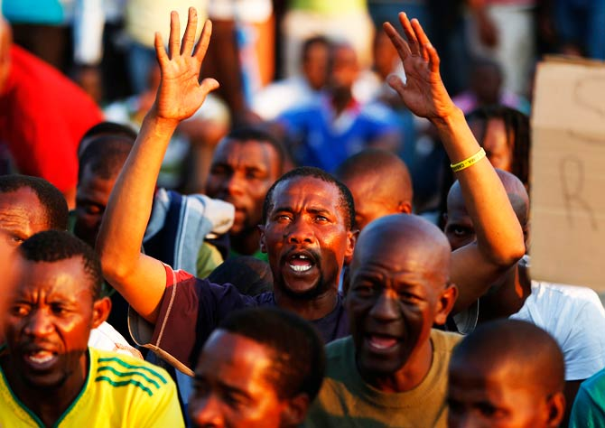 Platinum mineworkers react as they listen to a report back on negotiations at Lonmin's Marikana. – Photo by Reuters