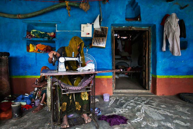 A woman uses a manual sewing machine inside her house. -Photo by Reuters.