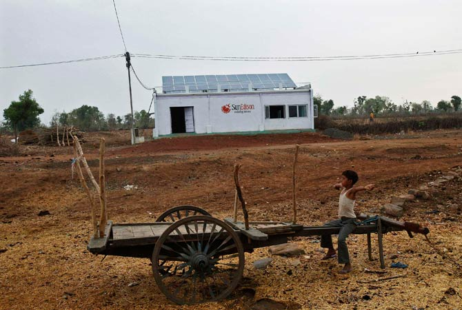 A boy sits on a cart in front of a solar power plant. -Photo by Reuters.