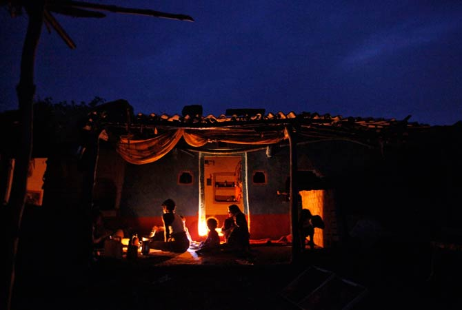 A family eats their dinner under the light of a kerosene lamp and battery operated torch inside their house. -Reuters.