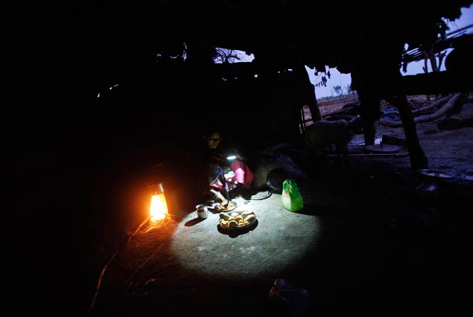 A woman uses a battery operated torch to prepare a meal inside the kitchen of her house. -Photo by Reuters.