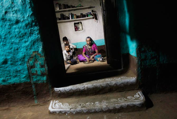 A family eats dinner inside their house illuminated by solar energy. -Photo by Reuters.