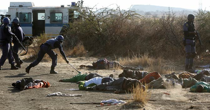 A policeman collects weapons that were supposedly used by protesting miners after they were shot outside a South African mine in Rustenburg, 100 km (62 miles) northwest of Johannesburg, August 16, 2012